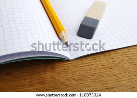 closeup of pencil notebook and eraser on wooden desk - stock photo