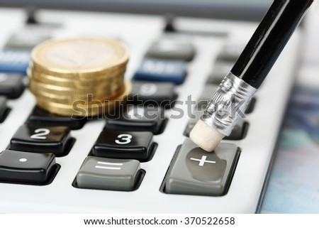closeup of pencil on calculator with coins - stock photo