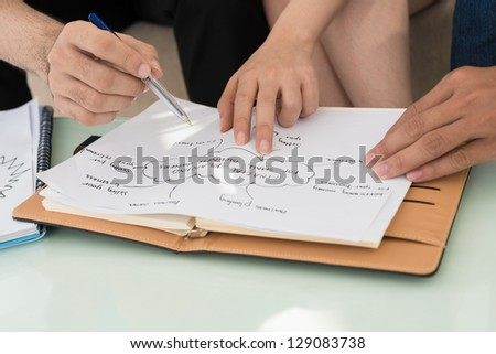 Closeup of people's hands working with the scheme - stock photo