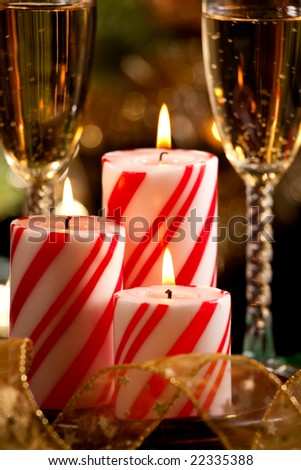 Closeup of peppermint candles, flutes of champagne and Christmas tree with lights out of focus in background. Shallow DOF.