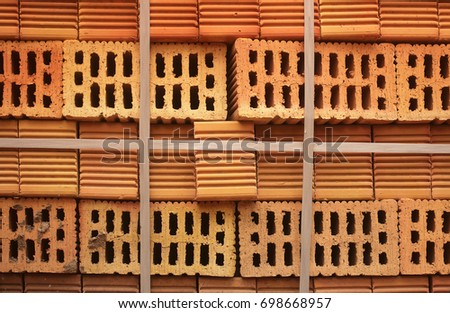 Closeup of perforated bright orange bricks stacked in a blocks