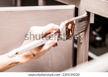 Closeup of Person Holding Paint Brush and Painting Kitchen Cabinets - stock photo