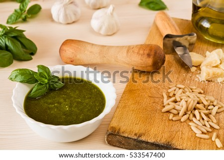 Closeup of pesto genovese with its ingredients over a table