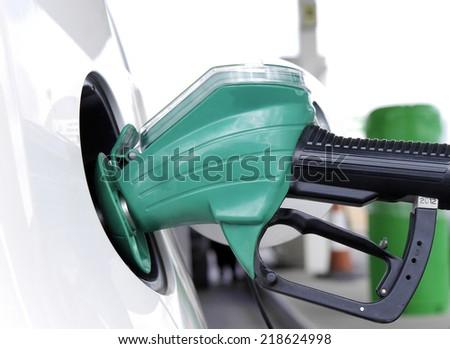 Closeup of petrol pump handle filling car with fuel - stock photo