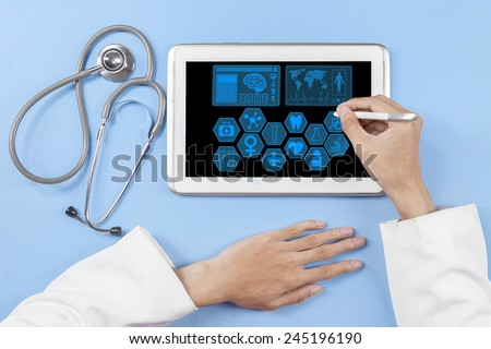 Closeup of physician hands with stethoscope and using a stylus pen to touch tablet screen - stock photo