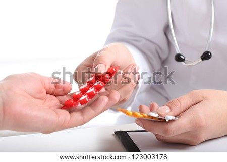 Closeup of physician's hands giving blisters of pills - stock photo