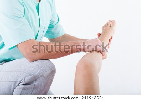 Closeup of physiotherapist bending knee of patient - stock photo