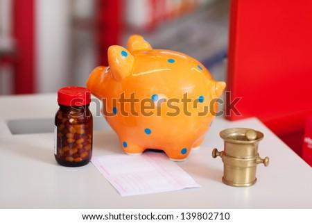 Closeup of piggybank, pill bottle, bill, mortar and pestle on table - stock photo