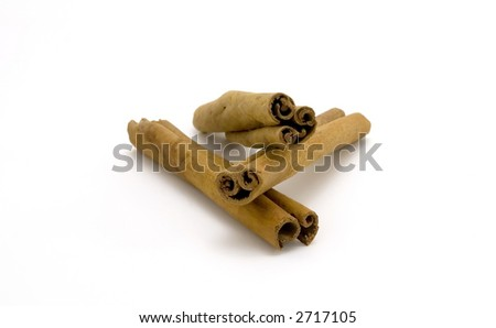 Closeup of pile of cinnamon sticks on a white background.