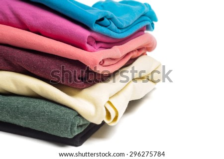 Closeup of pile of folded multicolored T-shirts isolated on white - stock photo