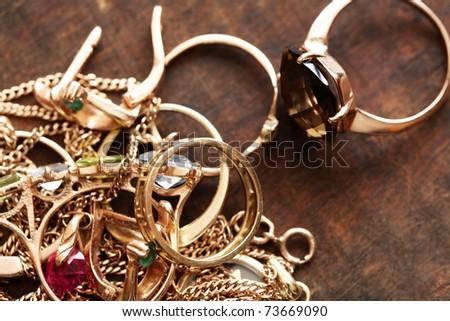 Closeup of pile of gold jewelry on wooden surface - stock photo