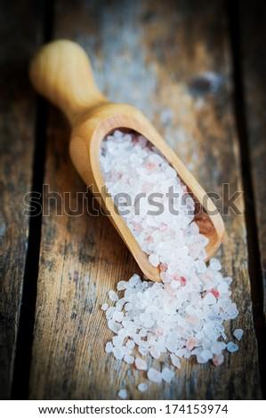 Closeup of pink himalayan salt on rustic wooden background - stock photo