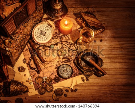 Closeup of pirates booty on wooden table, cigars smoke, glass of wine, map with way to search treasure, stolen antique jewelry, ancient money, adventure concept  - stock photo