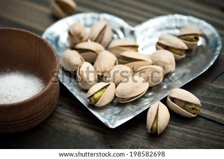 Closeup of pistachios nuts and salt on dark brown wooden table.  - stock photo