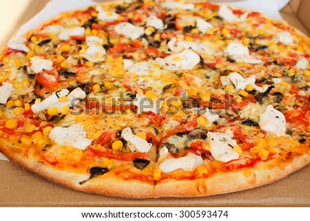 Closeup of pizza with chicken, tomatoes, corn, cheese, mushrooms and spices  - stock photo