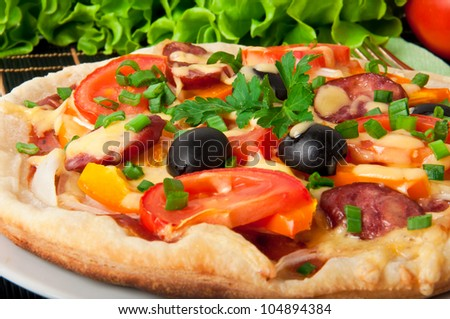 Closeup of pizza with tomatoes, cheese, black olives and peppers - stock photo