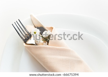 closeup of place setting with fork knife and little flower