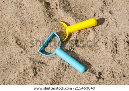 Closeup of plastic toys in a sandbox - conceptual sandbox level - stock photo