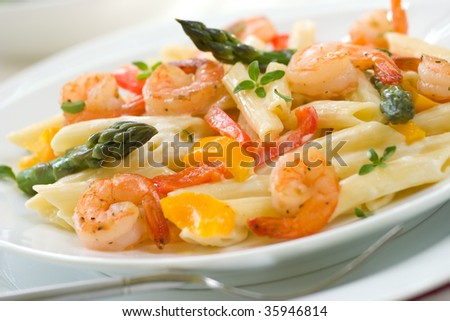 Closeup of plate of Shrimp Penne (tube-shaped pasta) with asparagus, bell pepper, origan and creamy Alfredo sauce . Shallow DOF - stock photo