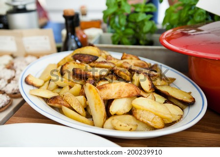 Closeup of plate of thick style french fries on table ready for serving at dinner party - stock photo