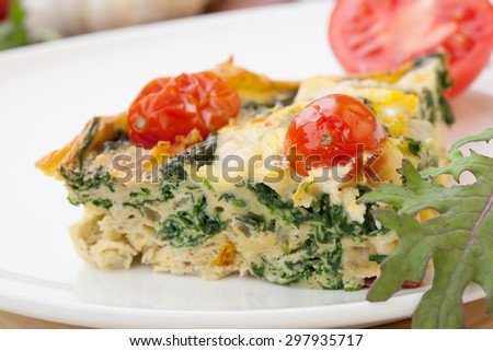 Closeup of plate with one piece of fresh made frittata, bread, and tomatoes. Pan with frittata with baby kale, sundried tomatoes, and goat cheese in background.