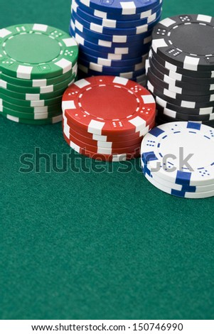 Closeup of poker chips in stacks on green felt card table surface - stock photo