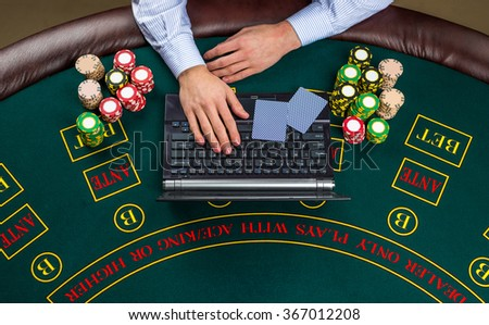 Closeup of poker player with playing cards, laptop and chips  - stock photo