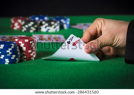 Closeup of poker player with two aces - stock photo