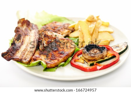 Closeup of pork meat steak, wedges potatoes and vegetables on a plate, isolated on white background