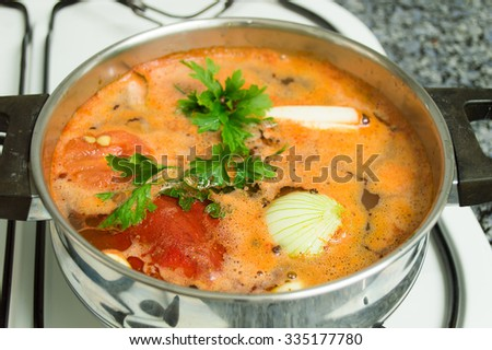 closeup of pot with some ingredientes to prepare a lentil stew on the kitchen stoves - stock photo