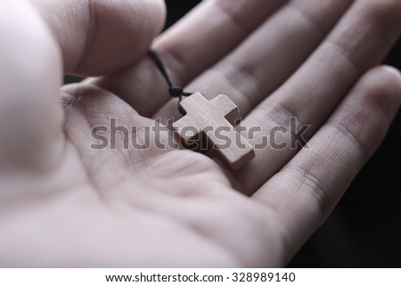 Closeup of praying hand holding the wooden cross. - stock photo