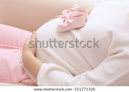 Closeup of pregnant woman holding baby shoes on her belly