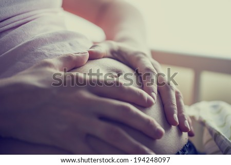 Closeup of pregnant woman holding her hands on her swollen belly shaping a heart, toned retro or instagram effect.