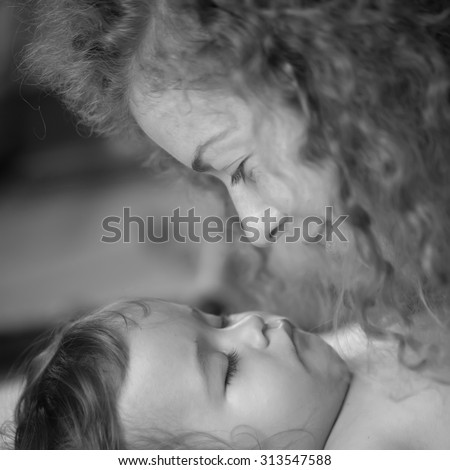 Closeup of pretty smiling loving mother with soft curly hair looking at small tiny cute male lovely baby sleeping indoor in bed with white linen black and white, square picture - stock photo