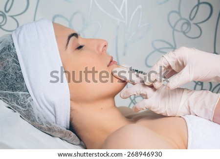 Closeup of pretty woman getting cosmetic injection in the lips like a part of the clinic treatment. Medicine, healthcare and beauty concept. - stock photo