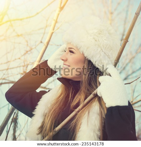 Closeup of pretty young blonde Caucasian woman in white faux fur hat and black coat outdoors in winter among tree branches. - stock photo