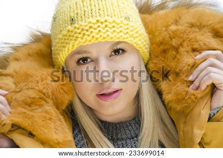 Closeup of pretty young woman in fashion winter clothes holding furry hood with her hands - stock photo