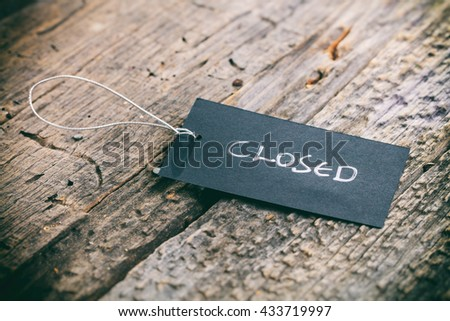 "Closeup of pricing tag with twine and ""Closed"" text on wooden background"