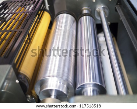 Closeup of printng machine working part with white light - stock photo