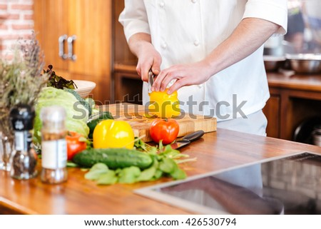 Closeup of professional chef cook in white uniform standing and cutting fresh yellow bell pepper on the kitchen - stock photo