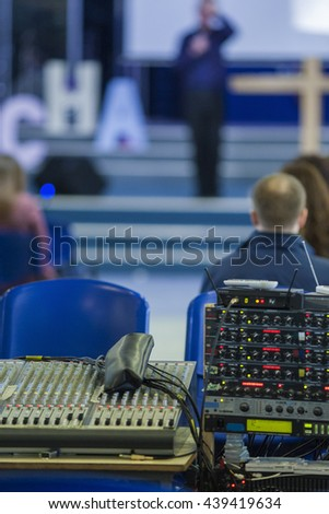 Closeup of Professional Mixing Console During Conference. With the Blurred Silhouette of  Spokesperson on a Background. Vertical Image - stock photo