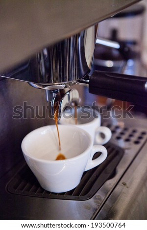 Closeup of professional standard espresso machine in cafe with coffee filtering into two cups from brewing group - stock photo
