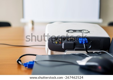 Closeup of projector for presentation connected to laptop with blank screen in front - stock photo