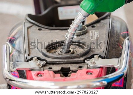 Closeup of pumping gasoline fuel into motorcycle tank