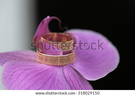 Closeup of purple fresh orchid flower with two beautiful wedding golden rings on dark blur backgroud, horizontal picture - stock photo