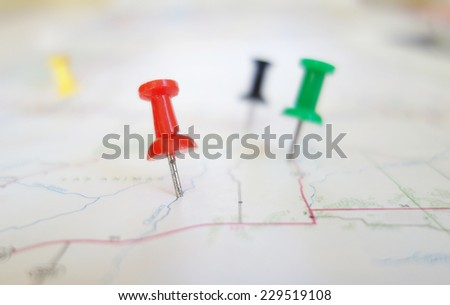 Closeup of push pin tacks in a map                                - stock photo