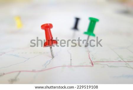 Closeup of push pin tacks in a map                                - stock photo