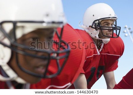 Closeup of quarterback waiting for snap against clear sky - stock photo