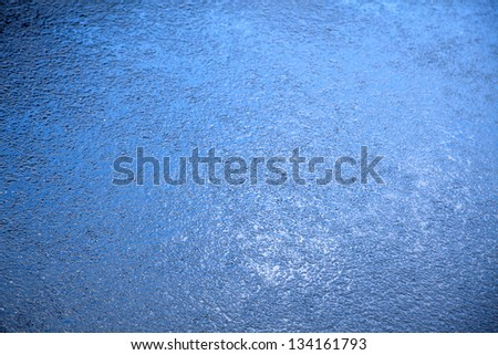Closeup of rain soaked asphalt, reflecting the blue color of the sky above.