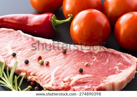 Closeup of raw New York strip steak and tomatoes on a black background. - stock photo